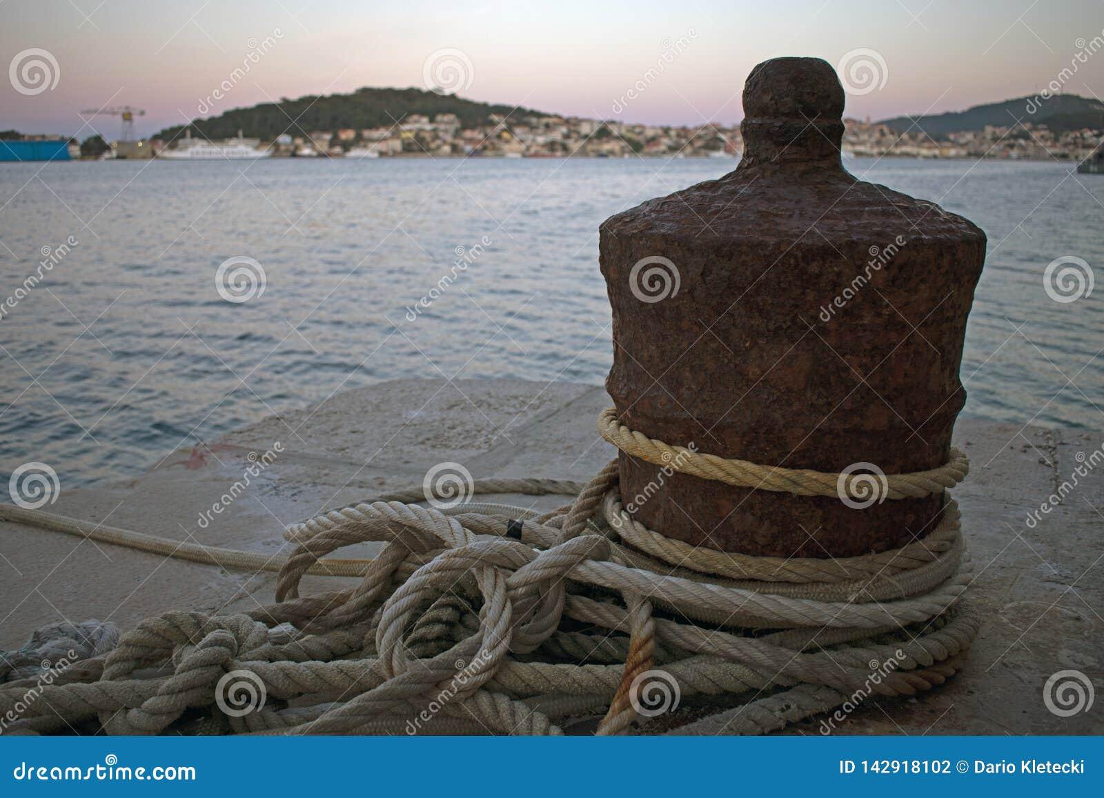 Ciérrese para arriba del amarre oxidado del barco con las cuerdas envueltas alrededor