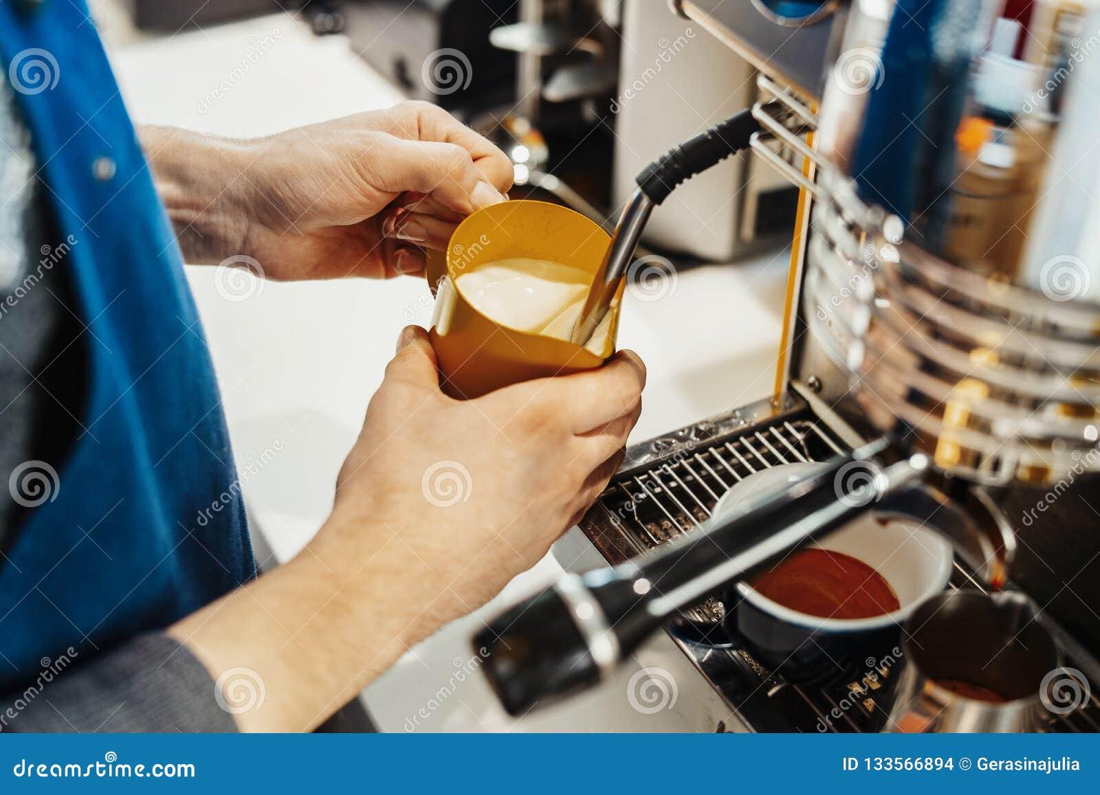 Ciérrese para arriba del barista que cuece la leche al vapor en la jarra con la máquina del café