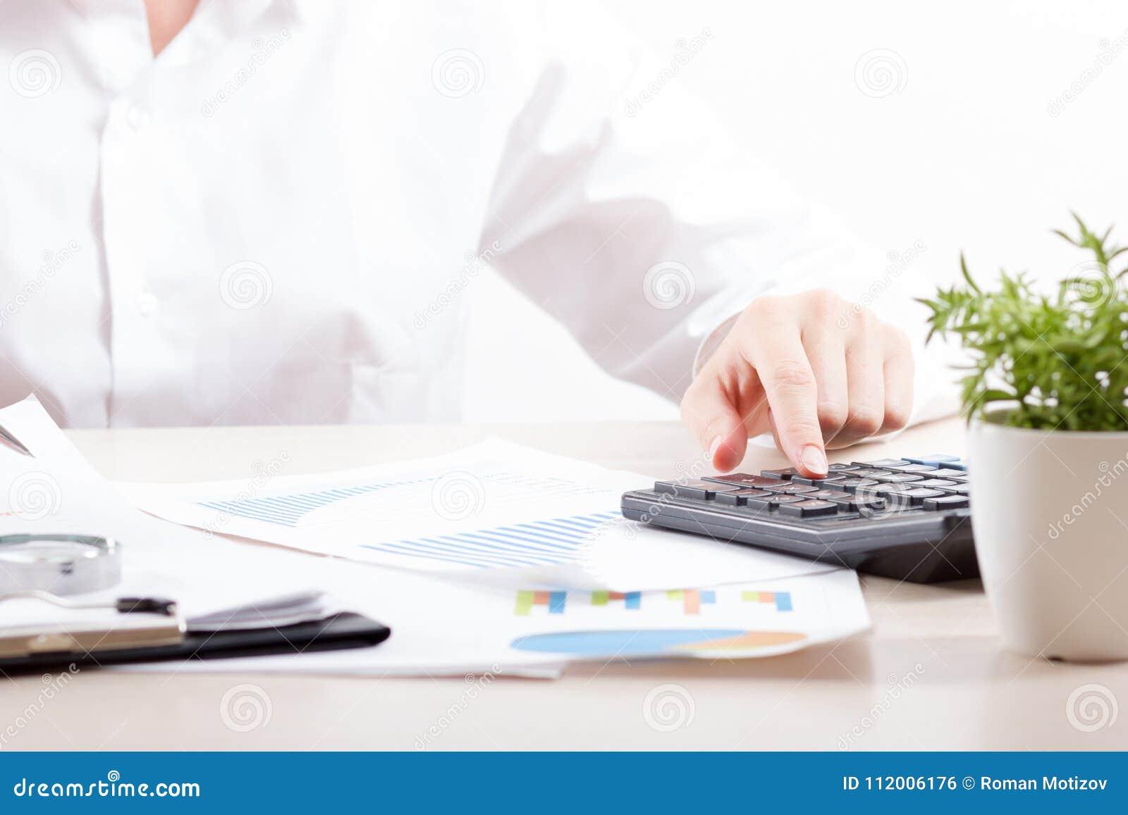 Ciérrese para arriba del contable o del banquero femenino que hace cálculos Ahorros, finanzas y concepto de la economía