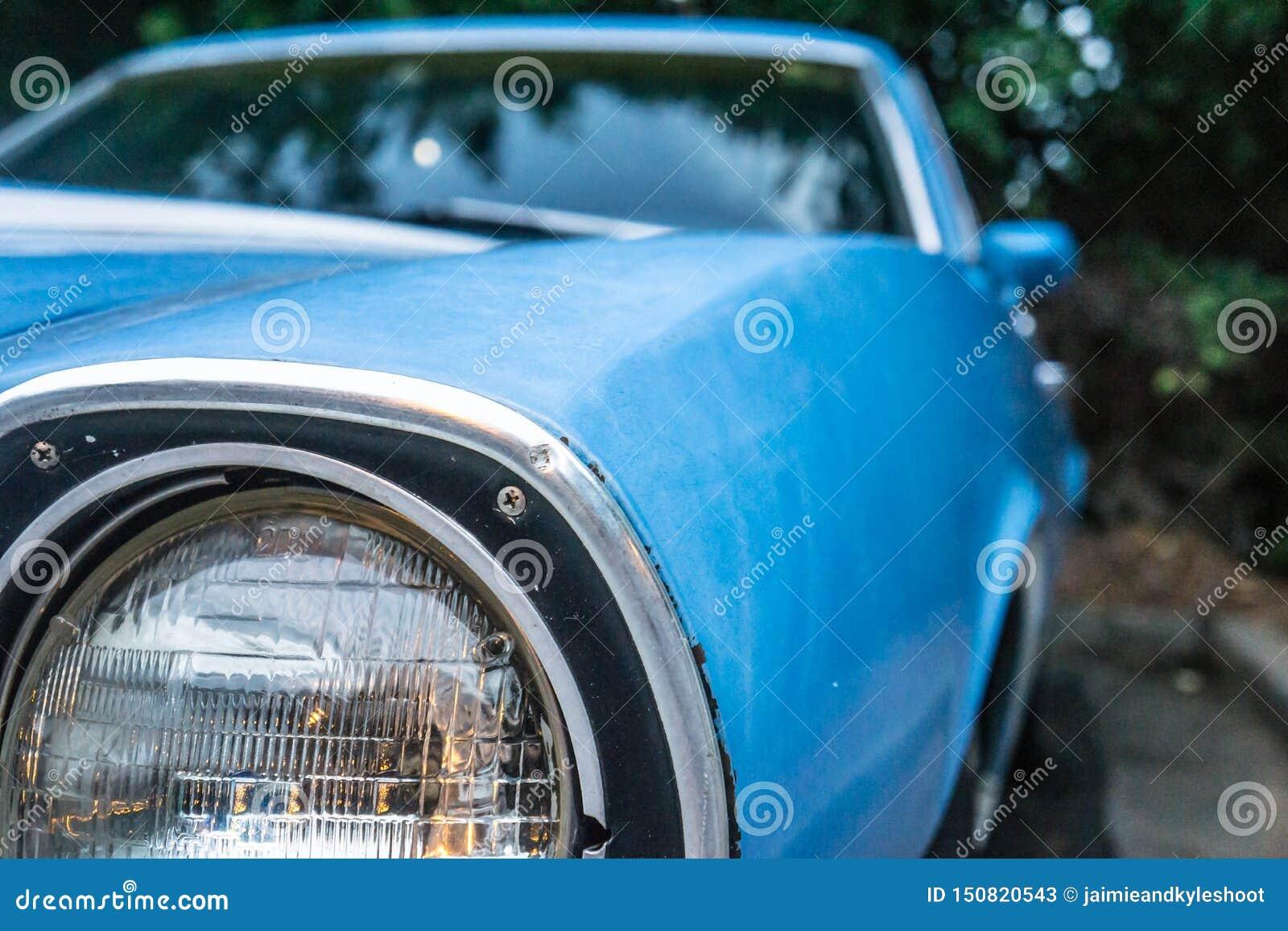 Ciérrese para arriba del faro viejo del coche azul del vintage Parqueado y rodeado por los árboles