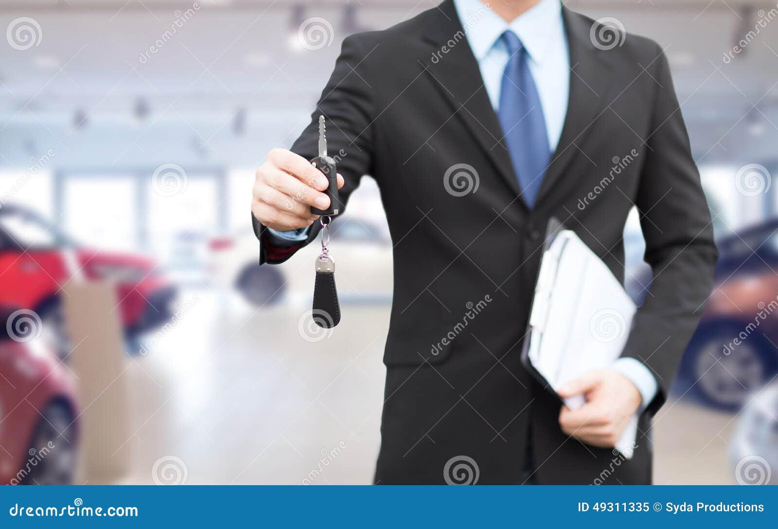 Ciérrese para arriba del hombre de negocios o del vendedor que da llave del coche