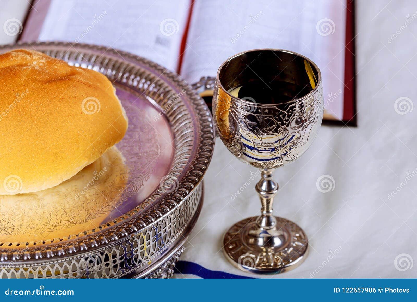 Ciérrese para arriba del pan y de una taza de vino rojo en la tabla de madera para la comunión, concepto cristiano para el record