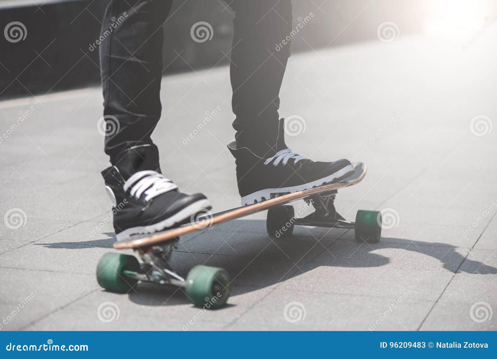 Ciérrese para arriba del skater& x27; piernas de s en el montar a caballo del longboard en la calle adentro al aire libre