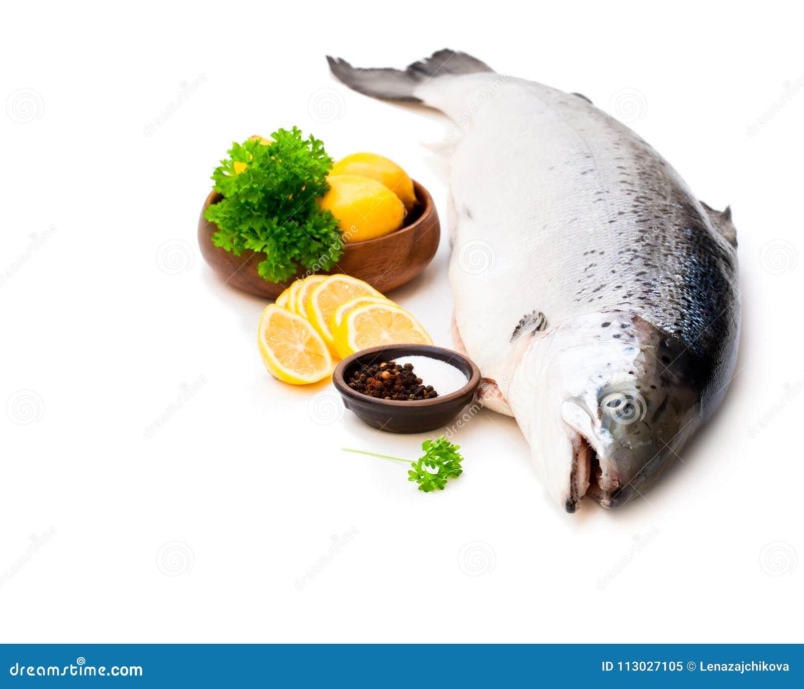 Ciérrese para arriba en un rawsalmon entero con el limón y la sal aislados en w