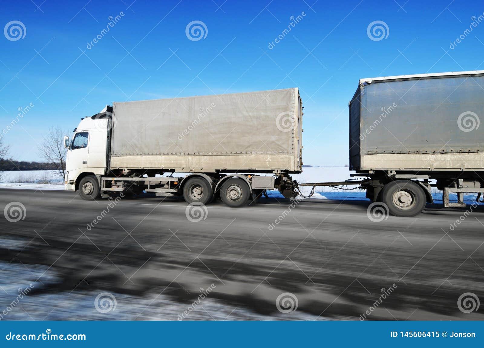 Ciężarówka z przyczepy jeżdżenia postem na zimy wsi drodze z śniegiem przeciw niebieskiemu niebu