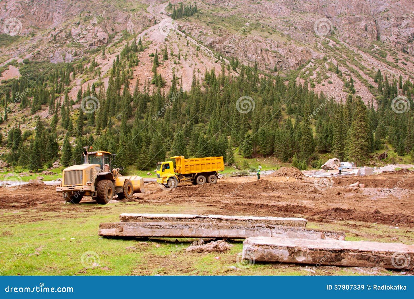 Ciężarówki na drodze podczas napraw po powodzi w dolinie między górami Środkowy Azja
