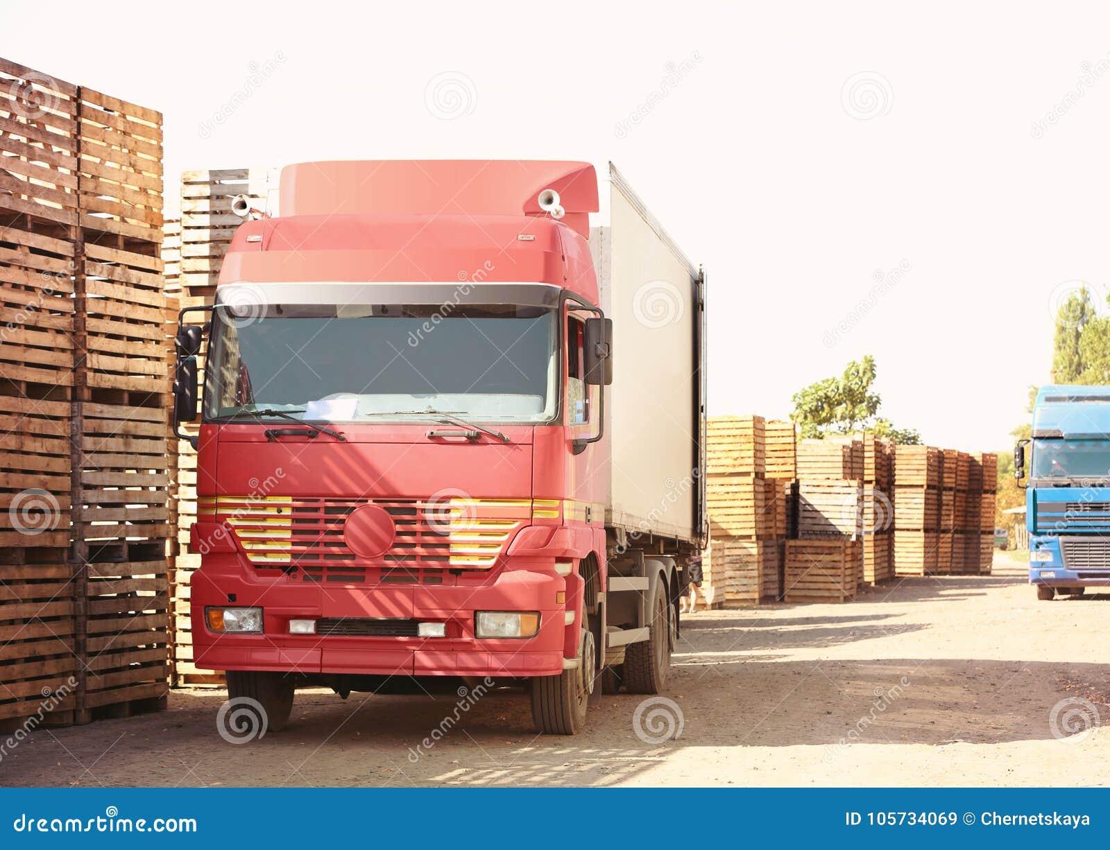 Ciężarówki obok pustych drewnianych skrzynek