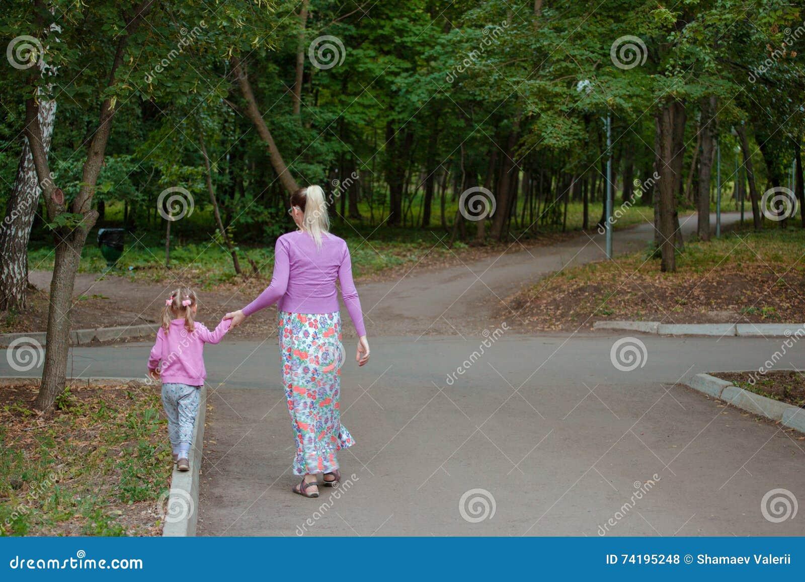 Ciężarna dziewczyna chodzi w parku