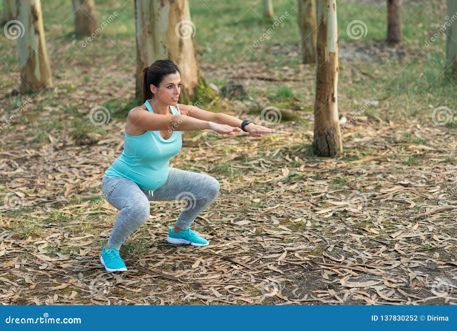 Ciężarna sprawności fizycznej kobieta robi kucnięciom plenerowym