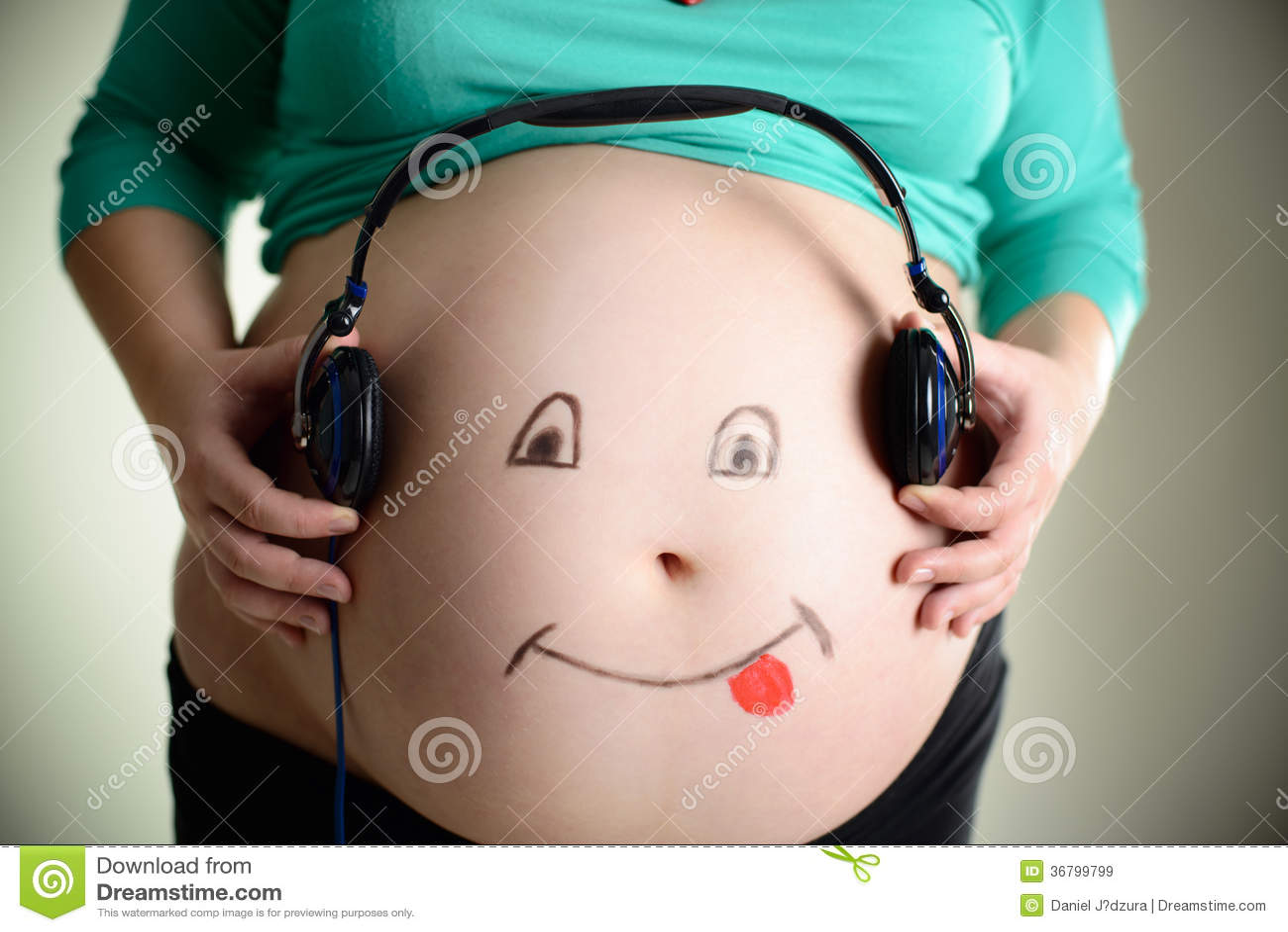 Ciężarny brzuch słucha muzyka przez hełmofonów