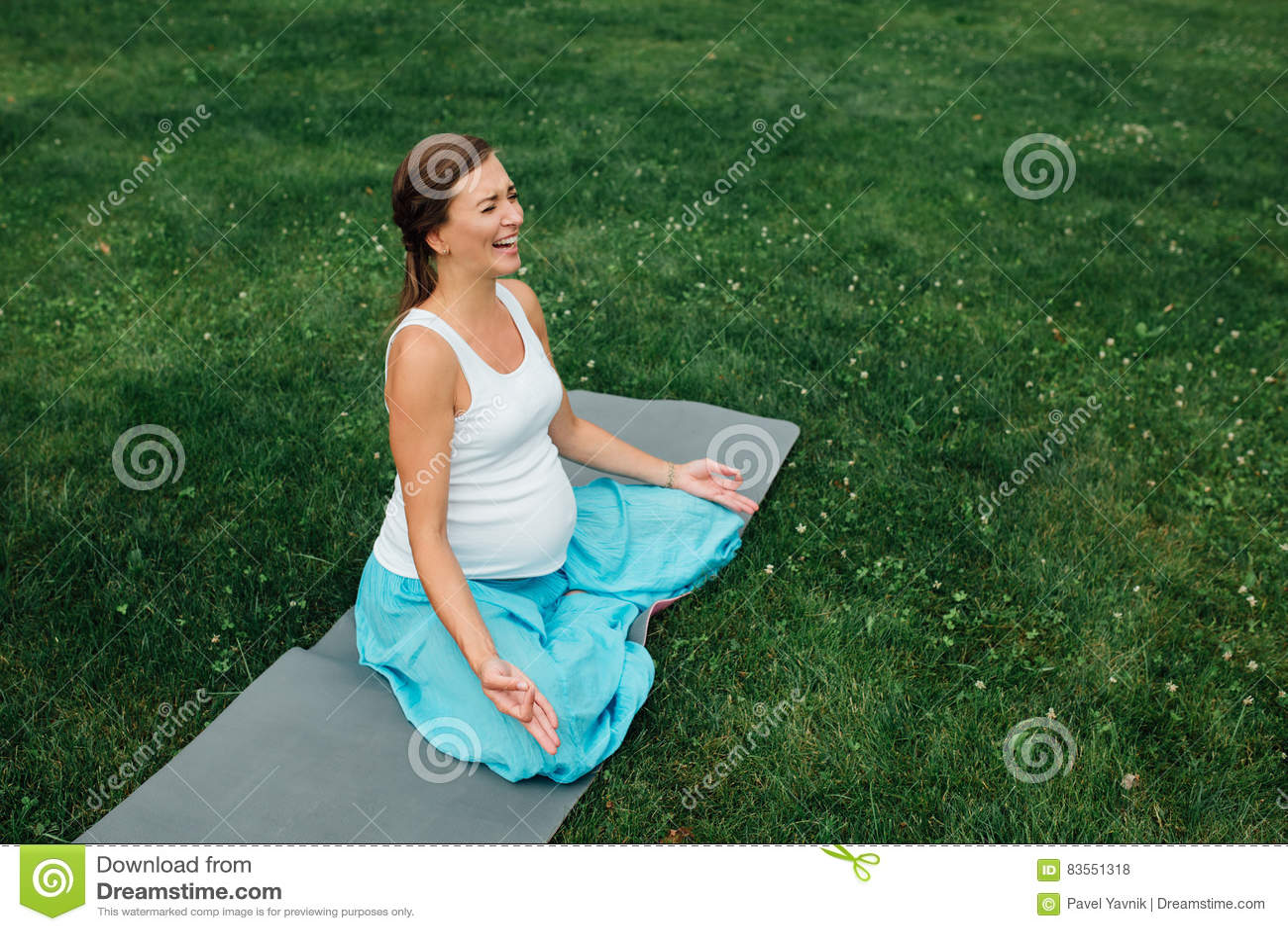 Ciężarny joga w lotosowej pozyci na lasowym tle w parku trawy mata, plenerowa, zdrowie kobieta