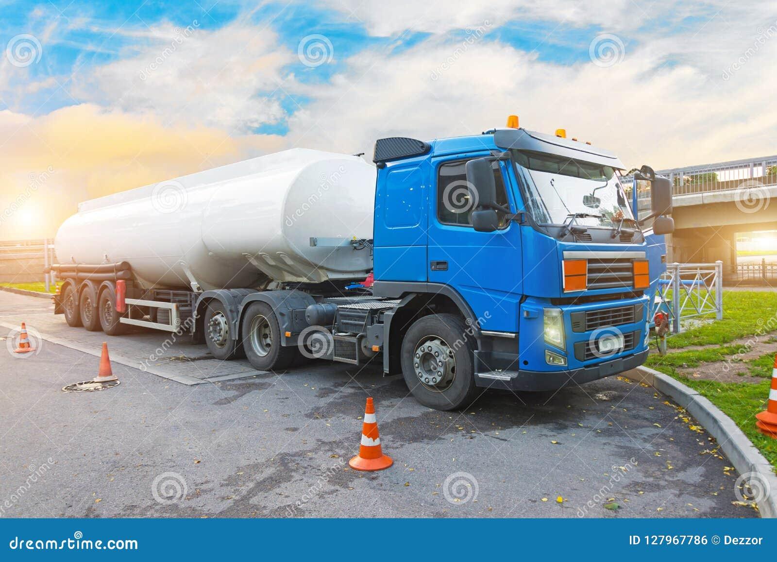 Ciężarowa paliwowa ciężarówka przed rozładowywać, z przyczepa zbiornikiem w parking przy benzynową stacją