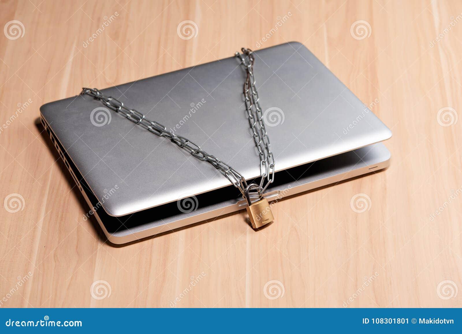 Ciężki łańcuch z kłódką wokoło laptopu na stole