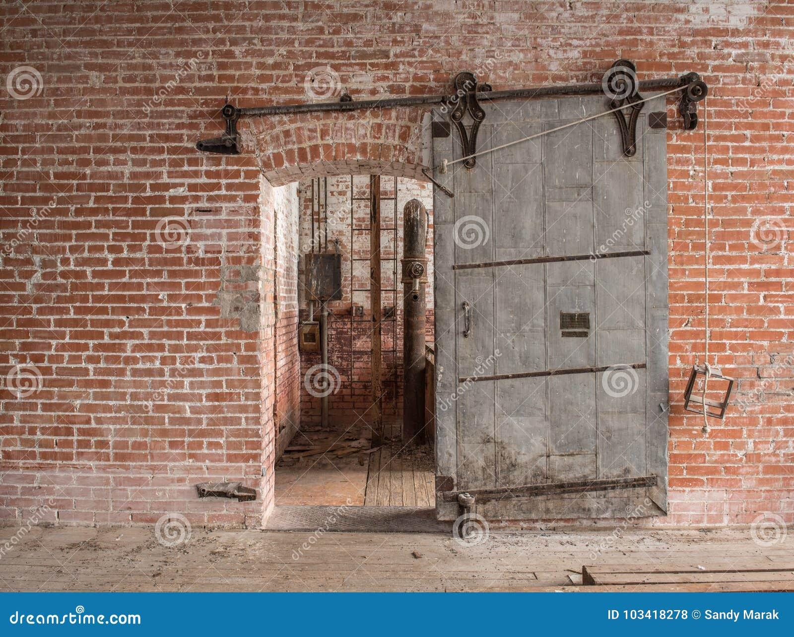 Ciężkiego ślizgowego metalu przemysłowy drzwi w starym magazynie