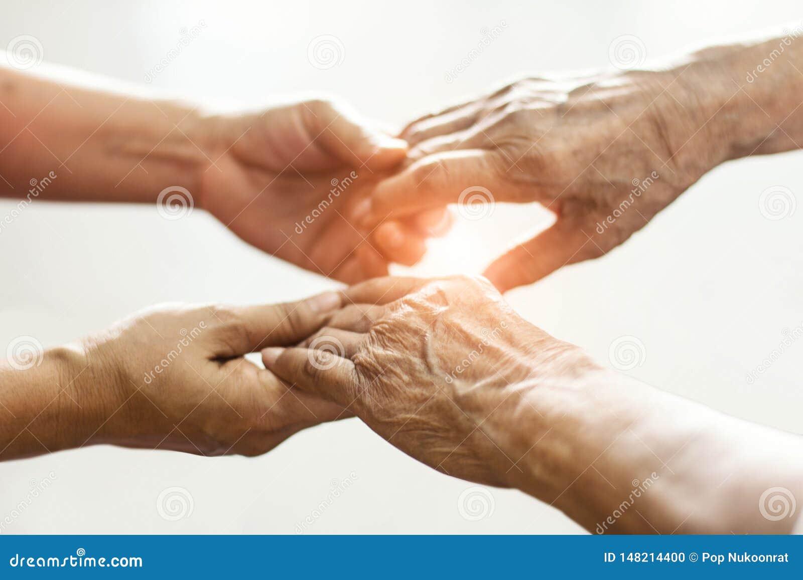 Ci?rrese encima de las manos de los cuidados en casa de los ancianos de las manos amigas Madre e hija