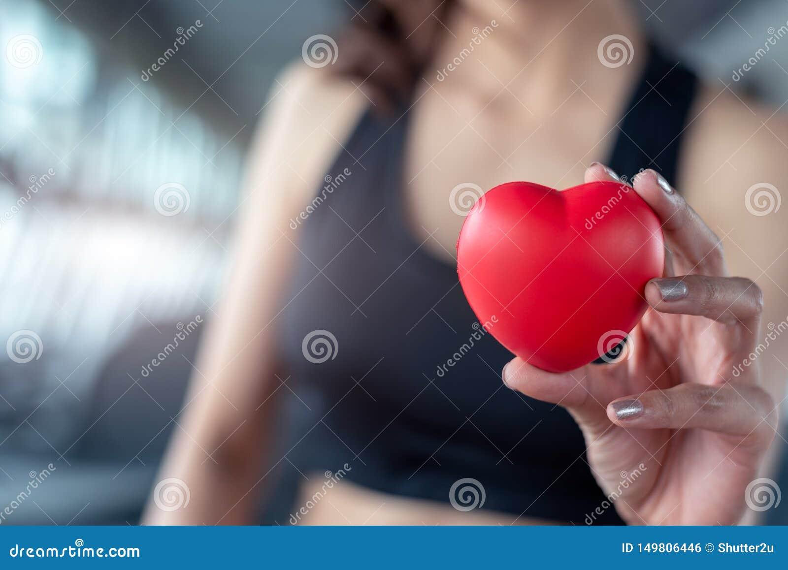 Ci?rrese para arriba de bola roja del masaje como forma del coraz?n en mano de la mujer de la aptitud en el centro de formaci?n d