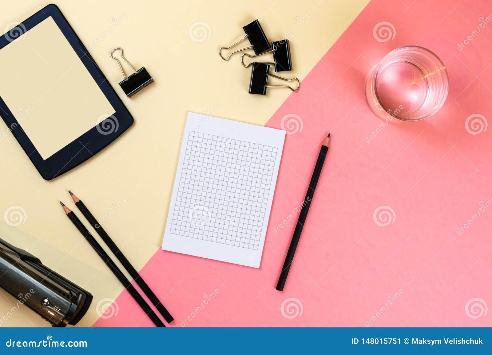 Ci?rrese para arriba de la mesa creativa de la oficina con las fuentes vac?as de la tableta y otros art?culos con el espacio de l