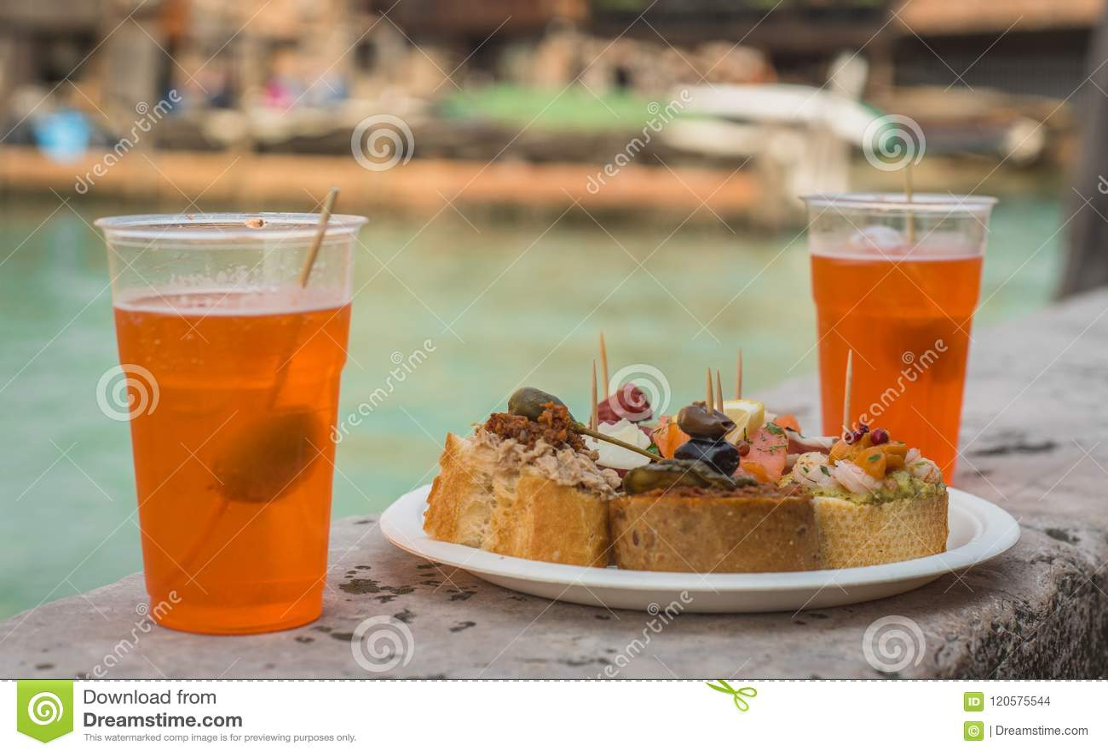 Cicchetti och att spritz i den Venetian kanalen