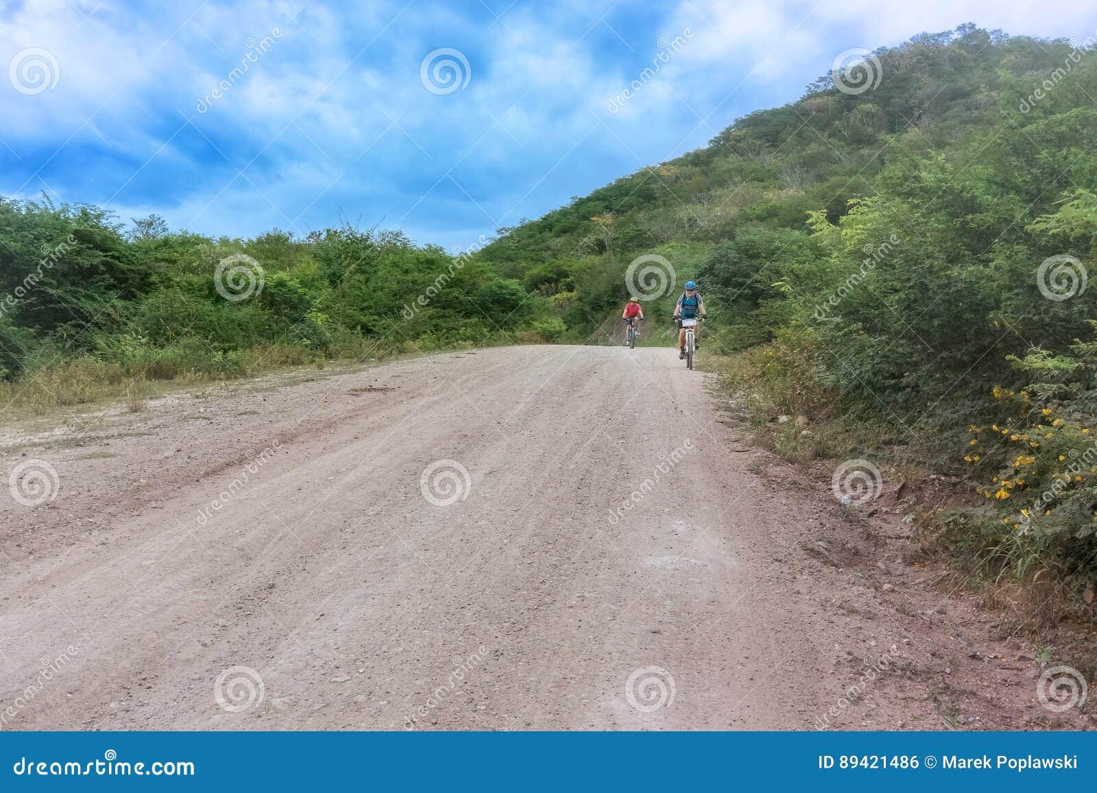 Ciclista dois na estrada através das montanhas nas Honduras