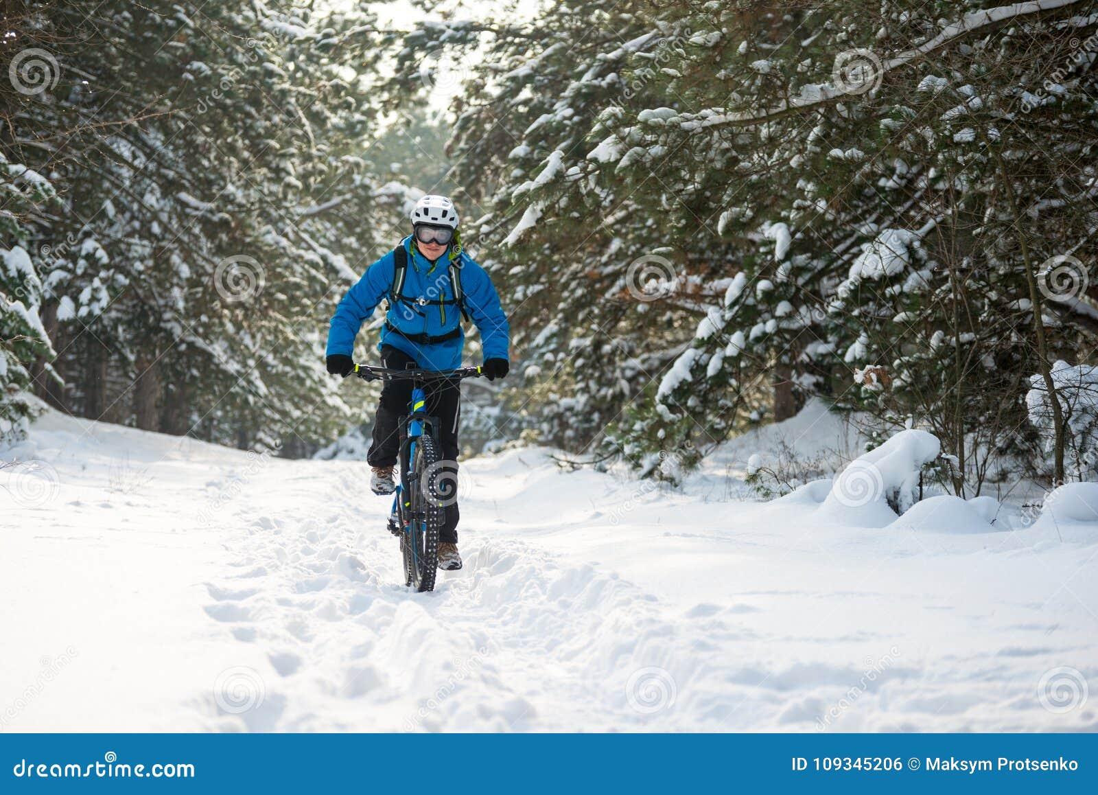 Ciclista en el azul que monta la bici de montaña en el invierno hermoso Forest Extreme Sport y el concepto Biking de Enduro