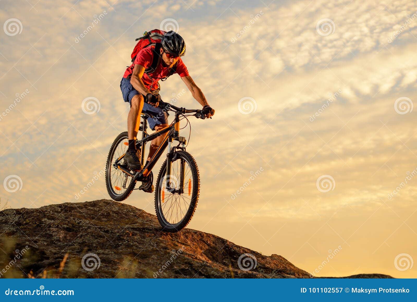 Ciclista en el rojo que monta la bici abajo de la roca en la puesta del sol Deporte extremo y concepto Biking de Enduro