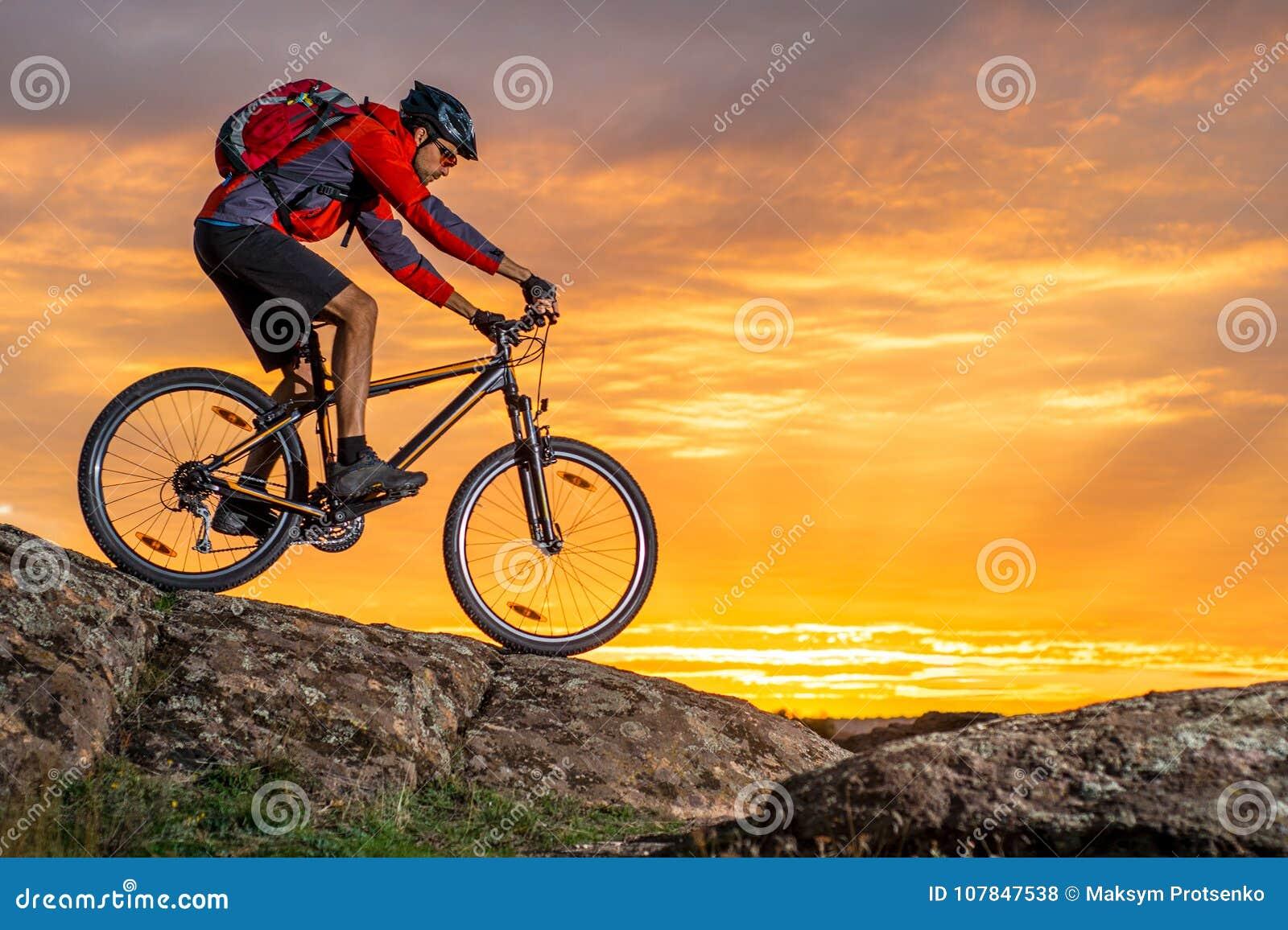 Ciclista en el rojo que monta la bici en Autumn Rocky Trail en la puesta del sol Deporte extremo y concepto Biking de Enduro