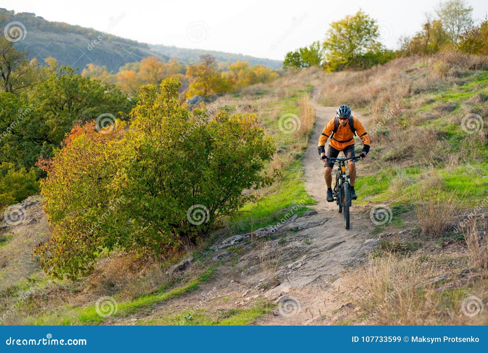 Ciclista en la naranja que monta la bici de montaña en Autumn Rocky Trail Deporte extremo y concepto Biking de Enduro