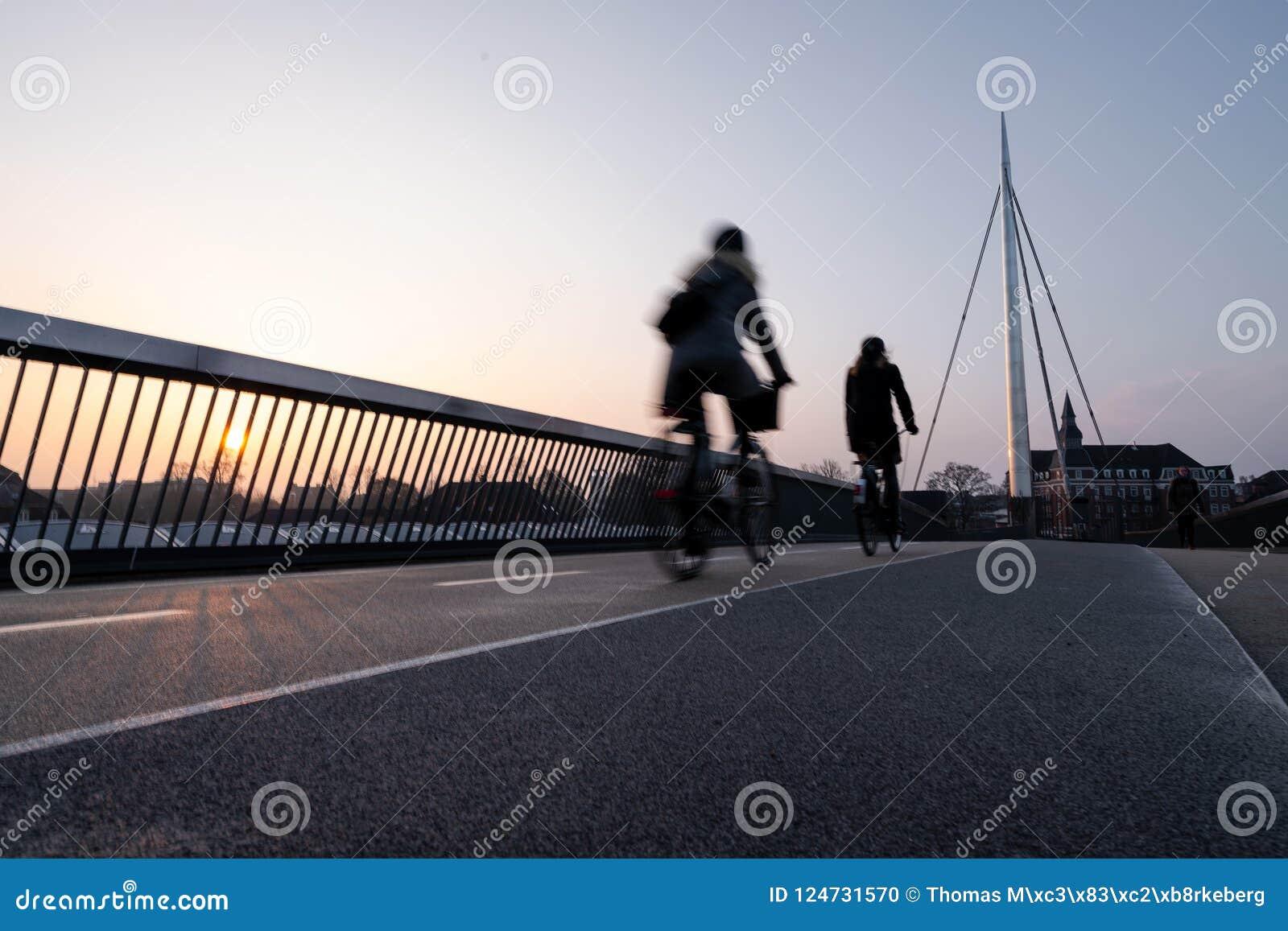 Ciclista en un puente de la bicicleta en Odense, Dinamarca