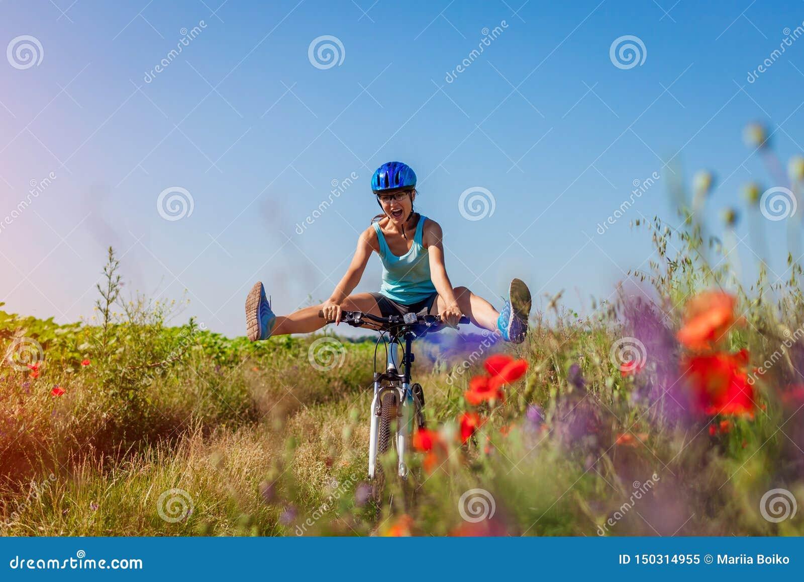 Ciclista felice della giovane donna che guida una bicicletta della montagna nel campo di estate Ragazza divertendosi le gambe di
