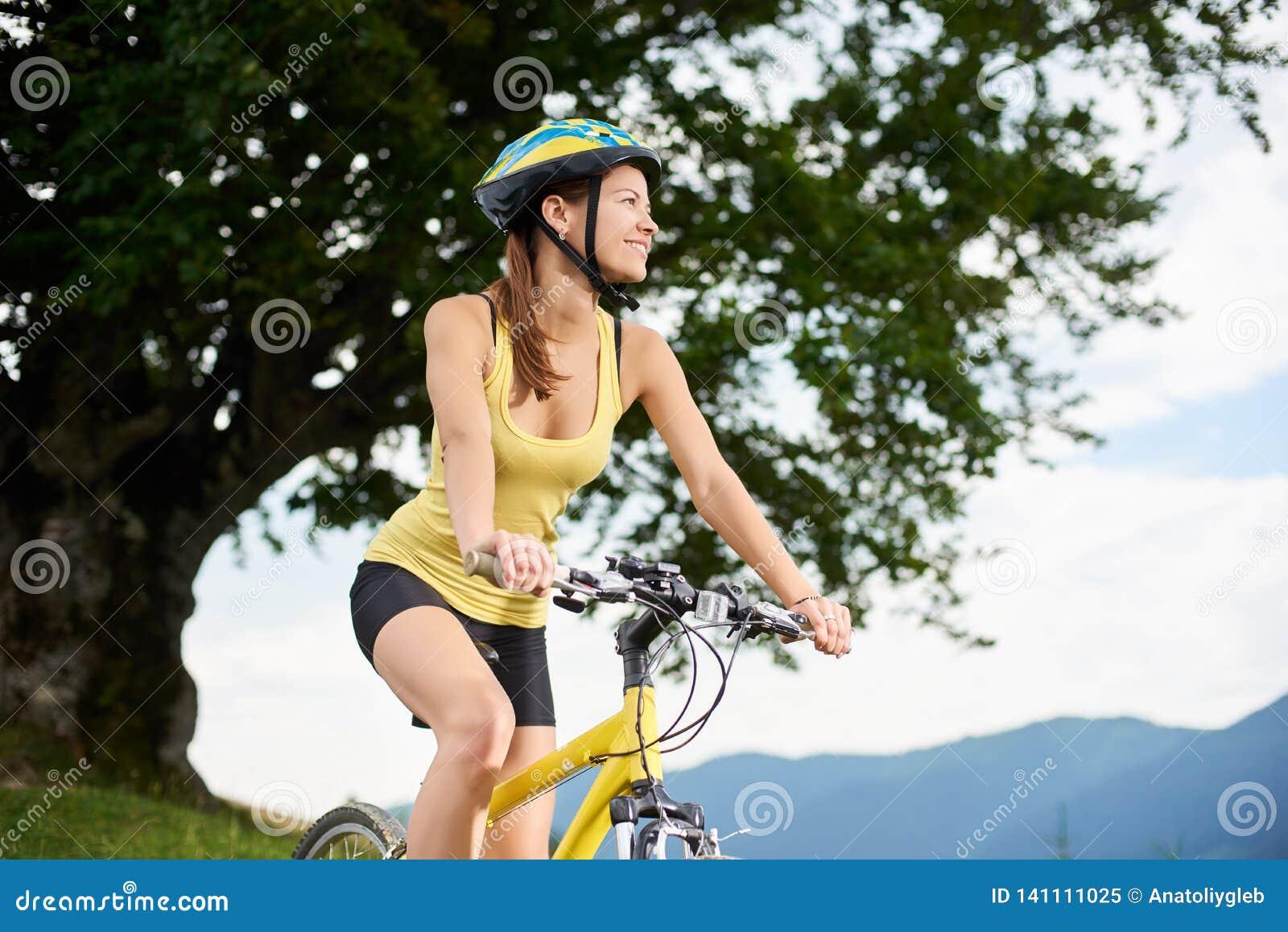 Ciclista femminile attraente con la bicicletta gialla della montagna, godente del giorno soleggiato nelle montagne