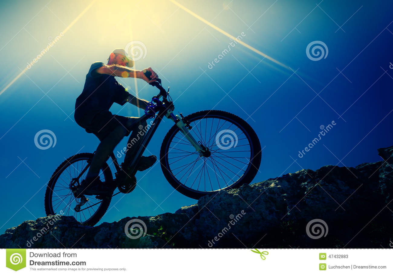 Ciclista masculino en una bici de montaña, retroiluminada
