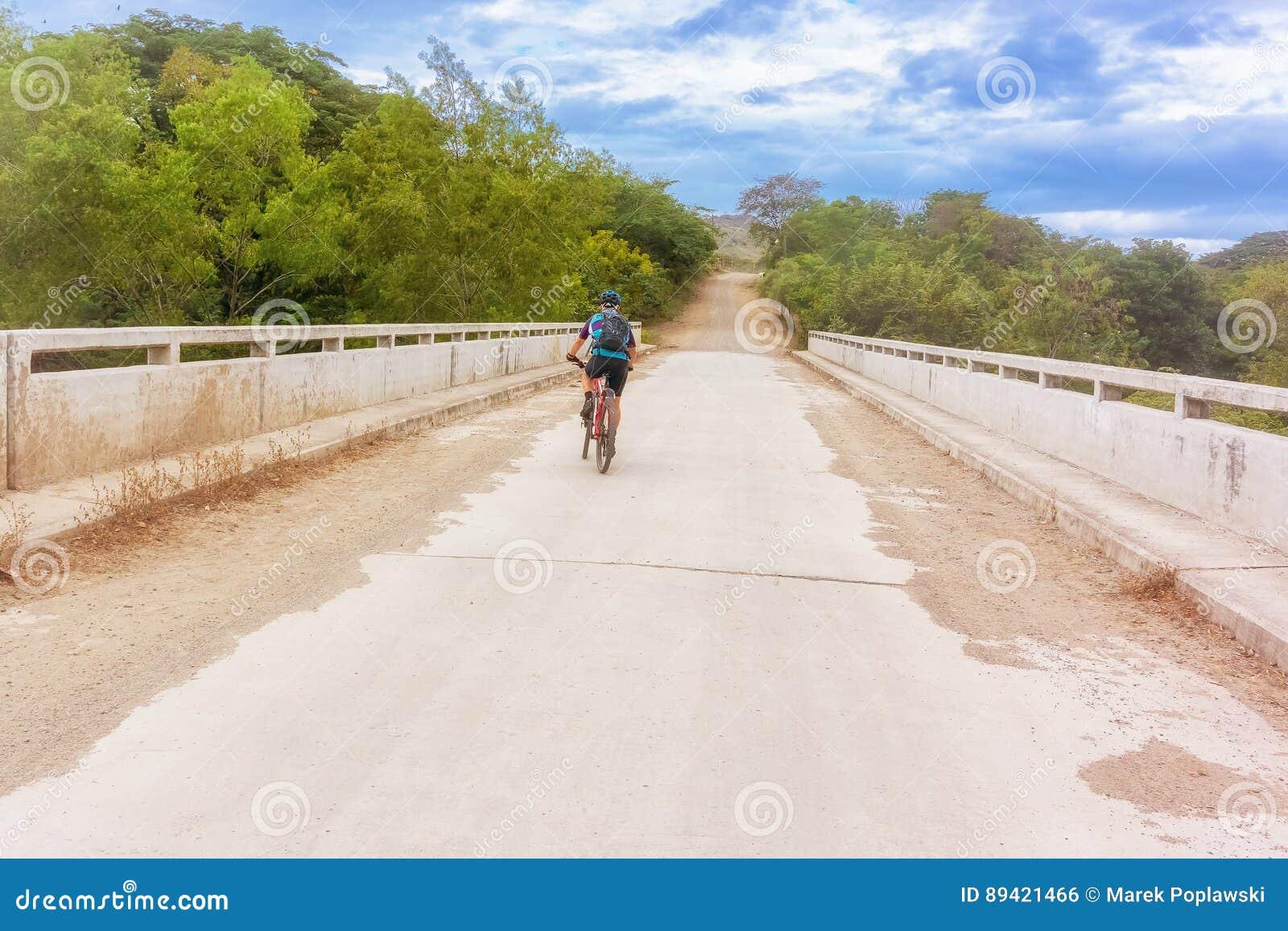 Ciclista na estrada do campo perto de Alauca nas Honduras
