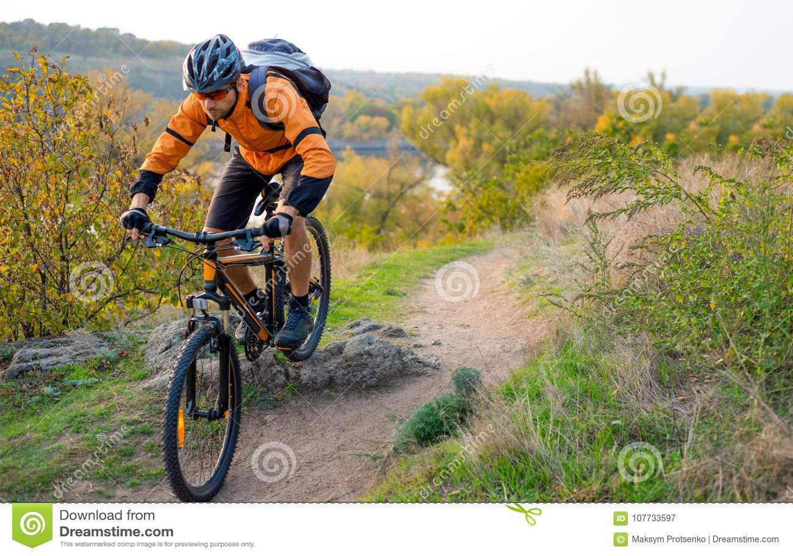 Ciclista na laranja que monta o Mountain bike em Autumn Rocky Trail Esporte extremo e conceito Biking de Enduro
