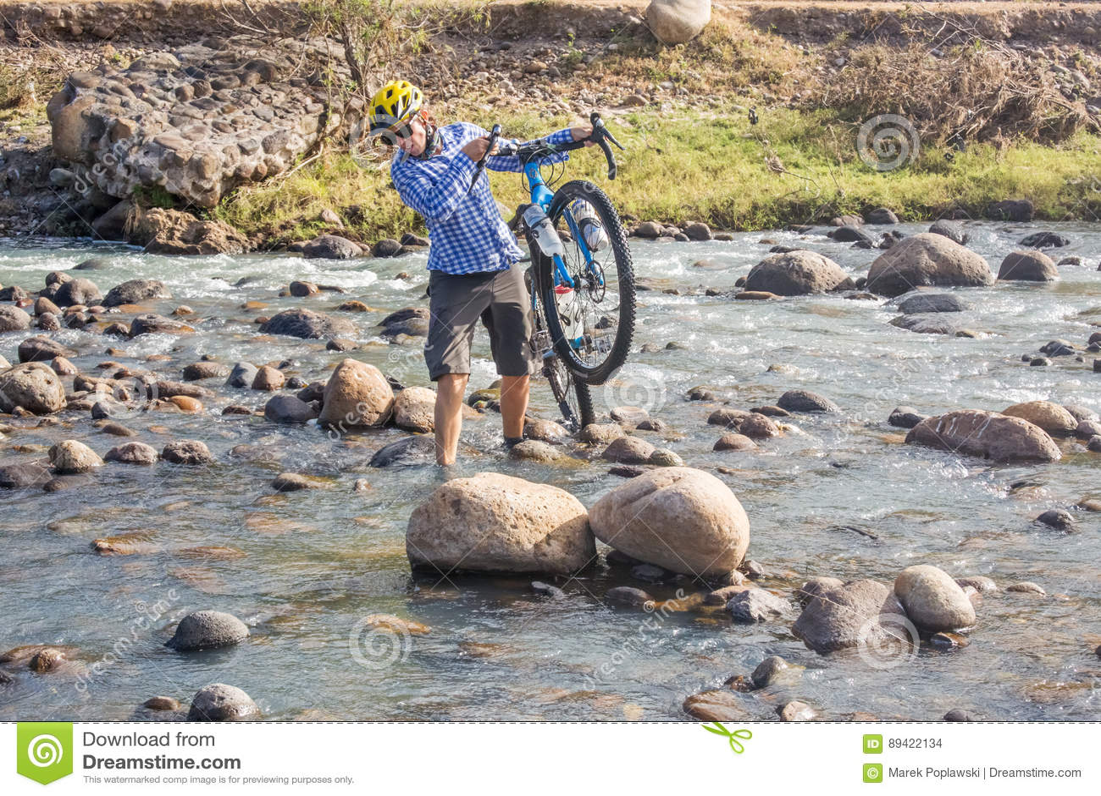 Ciclista que cruza Rio Humuya nas Honduras