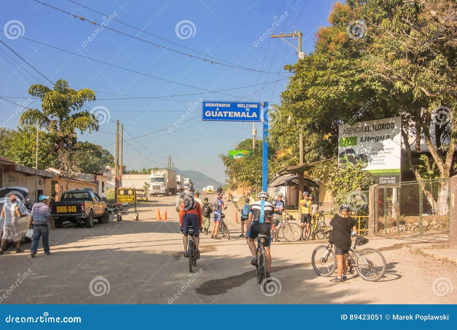 Ciclistas que cruzam a beira das Honduras à Guatemala
