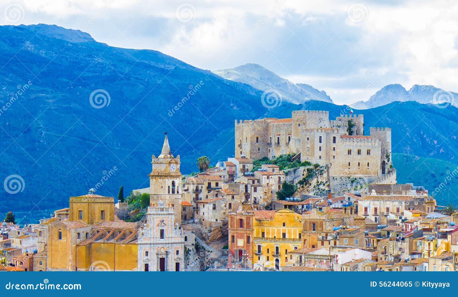 Cidade de Caccamo no monte com fundo das montanhas no dia nebuloso em Sicília