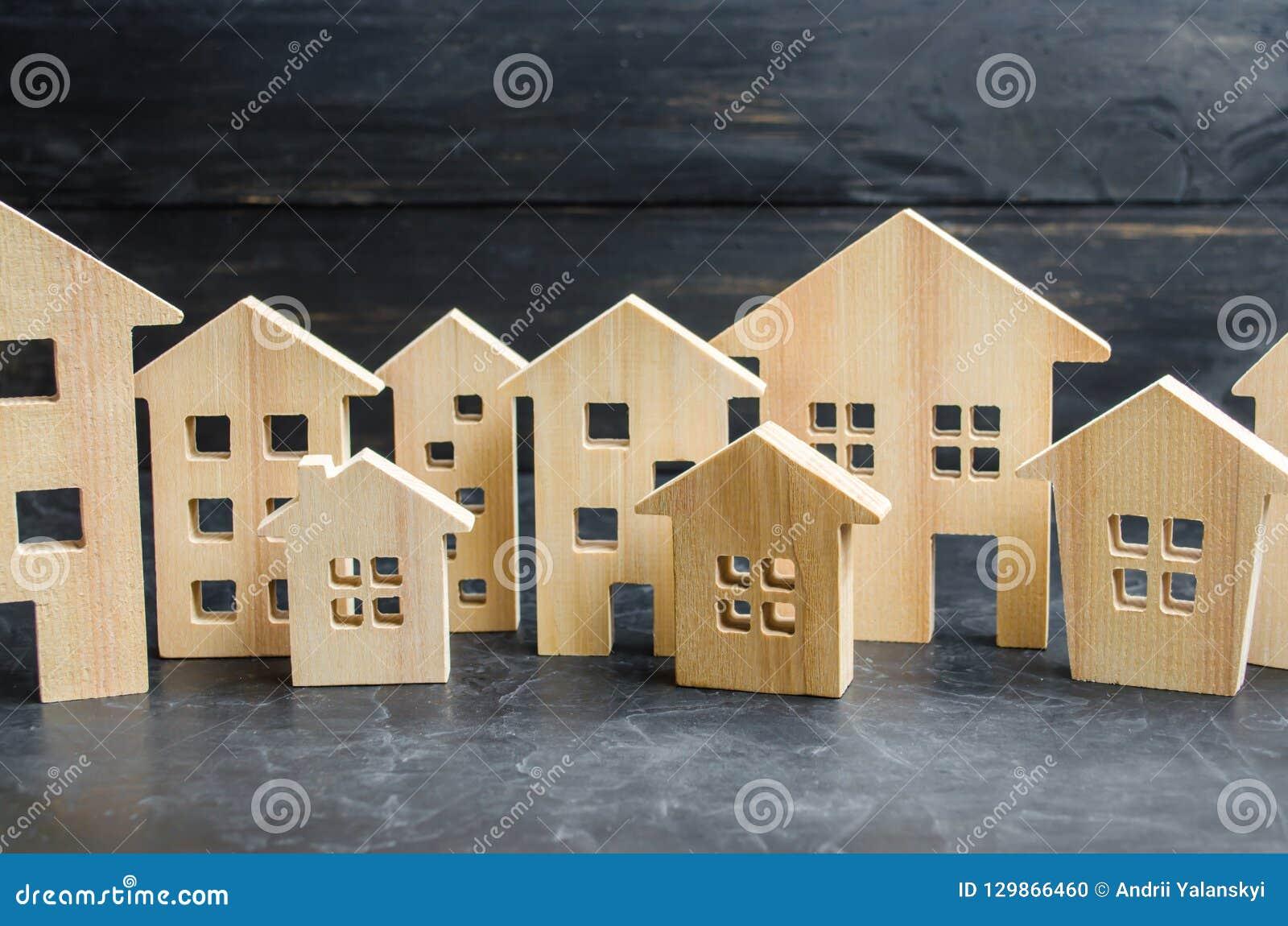 Cidade e casas de madeira conceito dos preços em subida para o abrigo ou o aluguel Aumento da procura para o abrigo e bens imobil