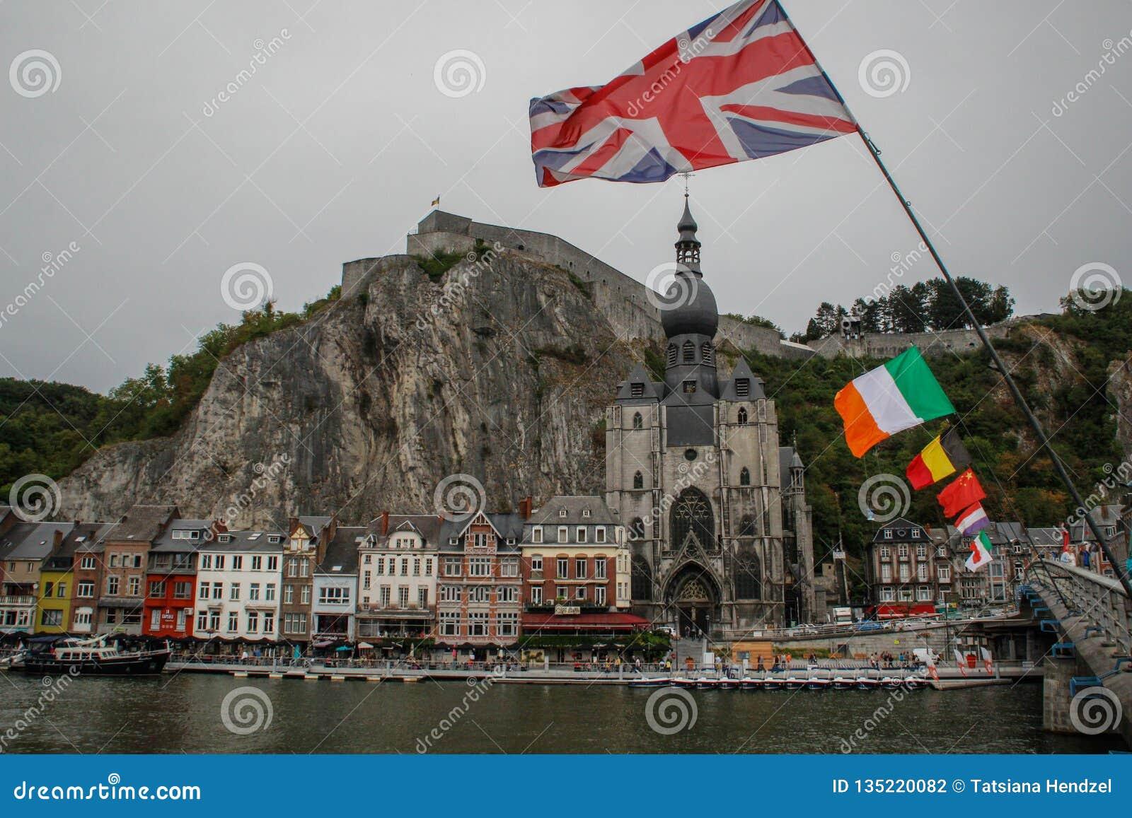 A cidade medieval antiga de Dinan, onde o saxofone foi inventado Vista das casas do rio e das bandeiras de países diferentes