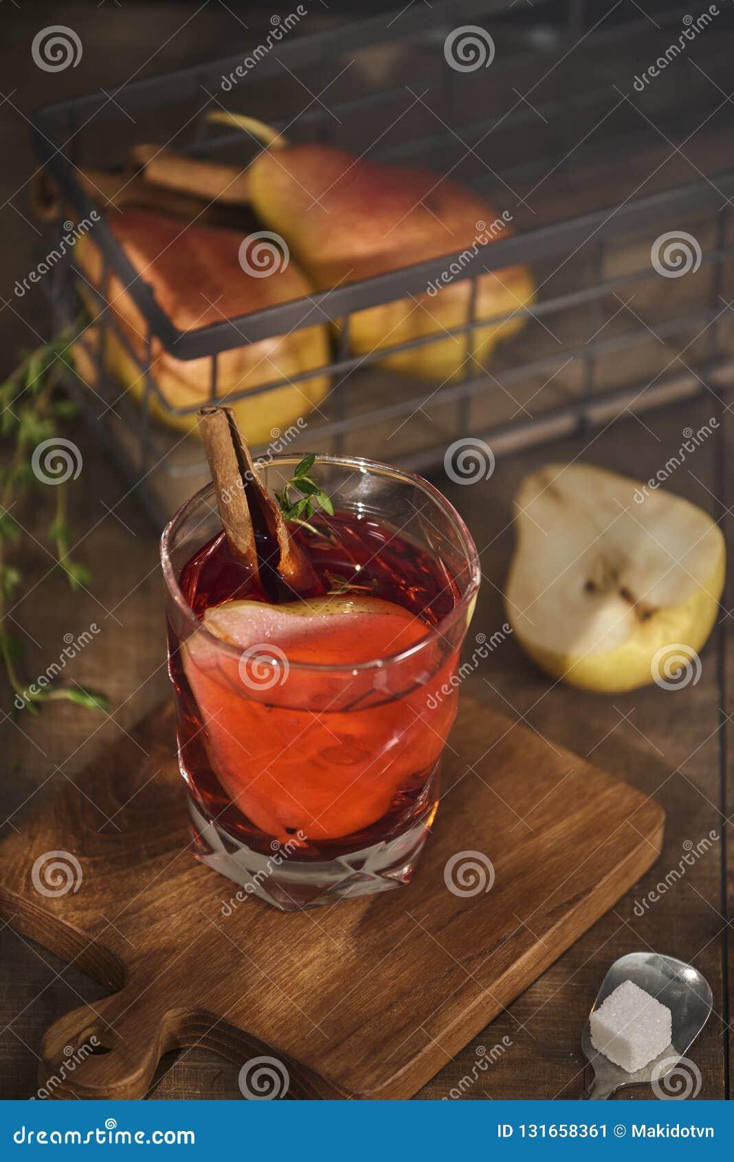 Cidre chauffé chaud fait maison de poire avec un bâton de cannelle sur un fond en bois