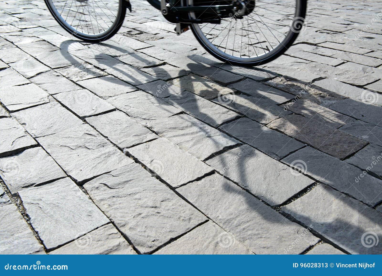 Cień cyklista na ulicie