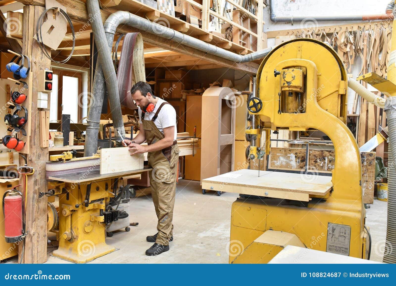 Cieśla pracuje w joinery - warsztat dla woodworking i sawi