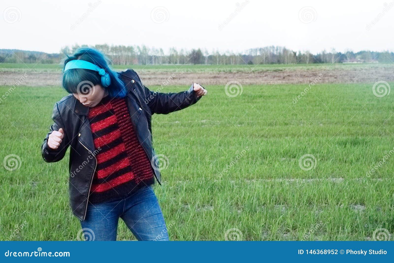 Ciekawa dziewczyna w b??kitnym w?osy, s?ucha muzyka i tanczy w polu