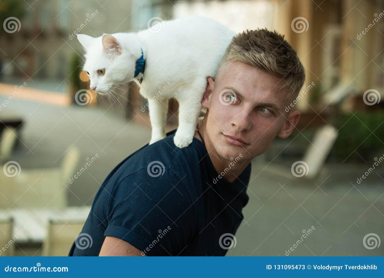 Ciekawy badacz Szczęśliwy mężczyzna na spacerze z kota zwierzęciem domowym Mięśniowego mężczyzny chwyta śliczny zarodowy kot Szcz
