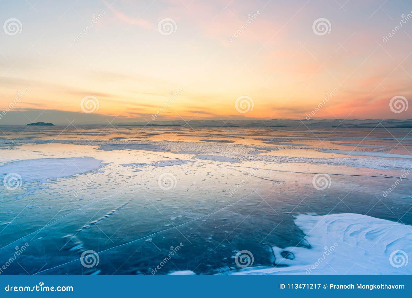 Ciel de lever de soleil au-dessus de lac d eau glacée avec le fond d horizon