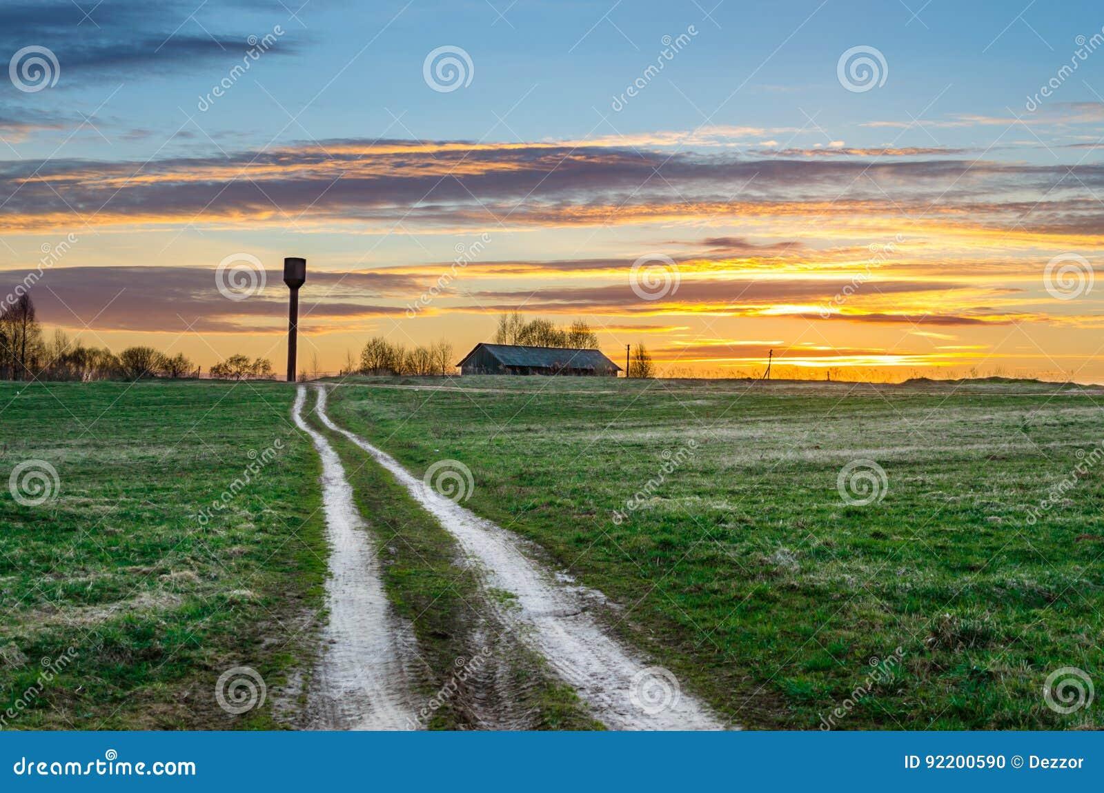 Ciel de soirée à la route de coucher du soleil dans le domaine menant à la tour de grange et d eau de hangar du paysage rural du