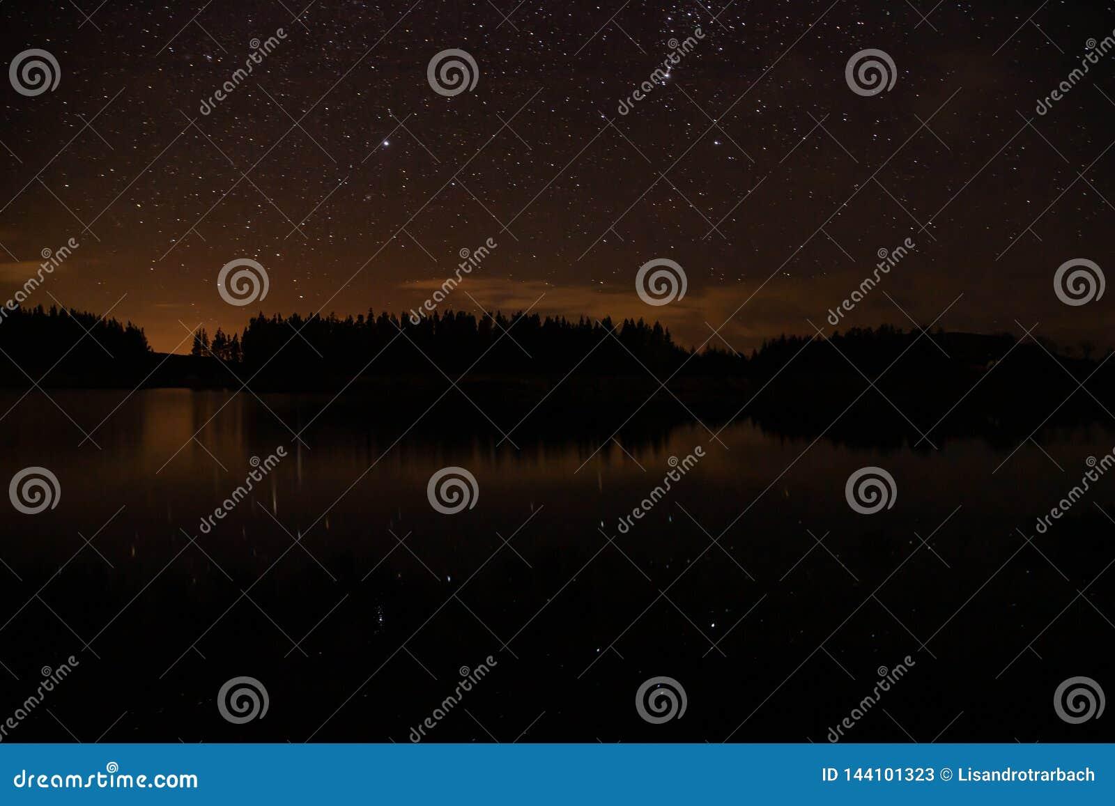 Ciel nocturne avec des débuts dans un lac Conemara avec la forêt de pin autour