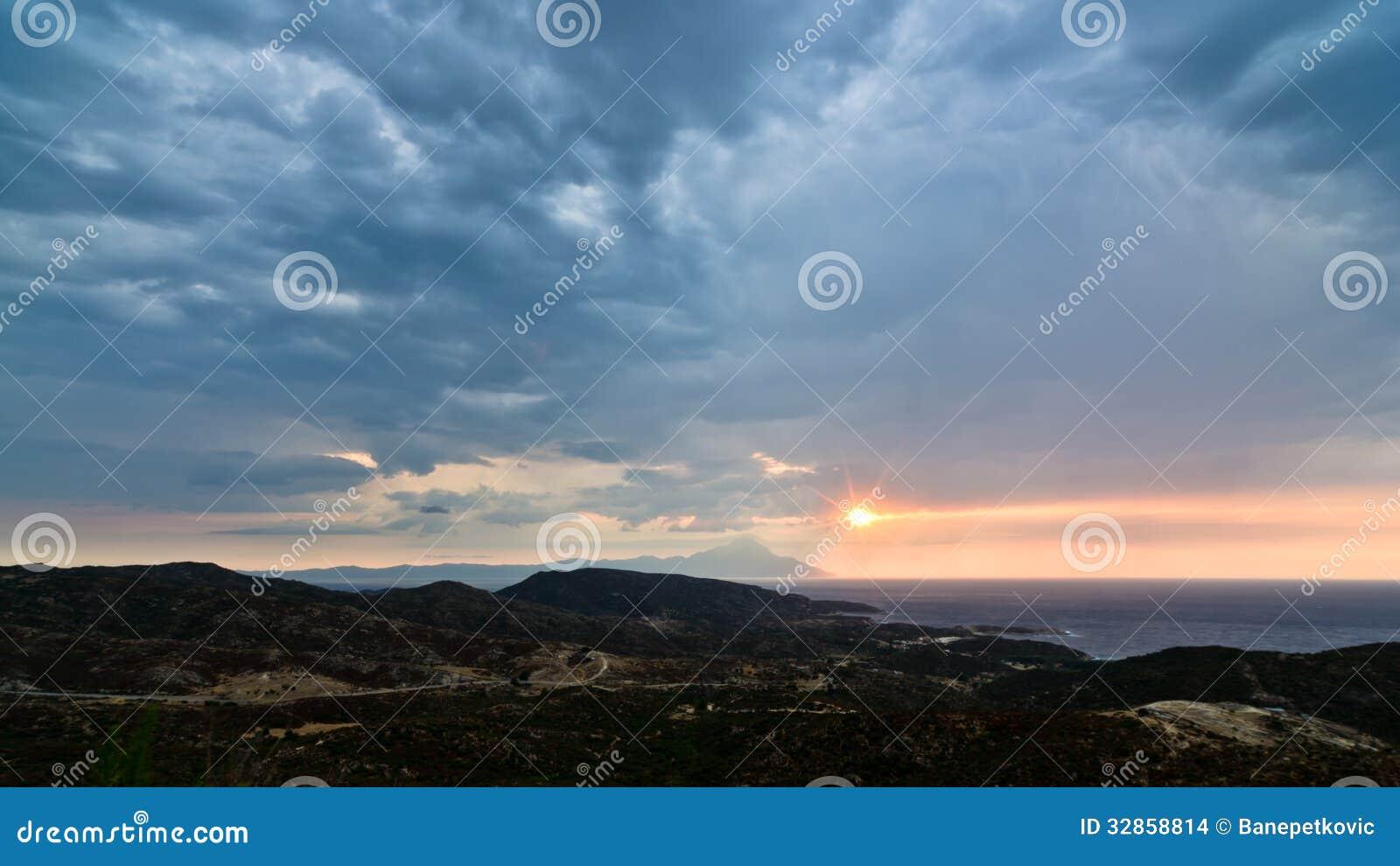 Ciel orageux, lever de soleil en mer et paysage autour de montagne sainte Athos