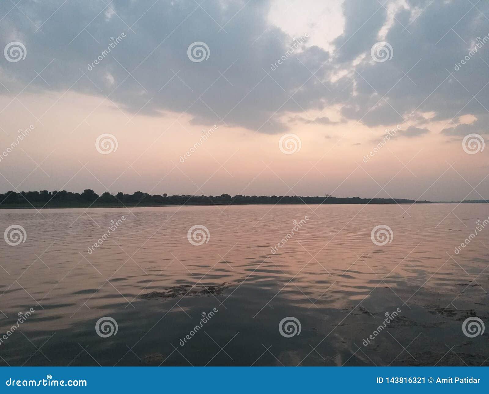 Cielo anaranjado de la puesta del sol de la imagen de fondo en el río