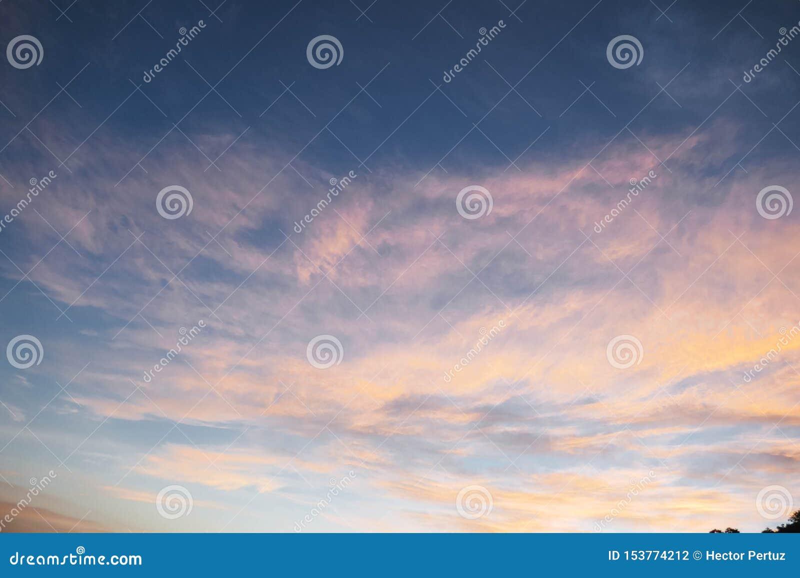 Cielo azul con la nube y la puesta del sol