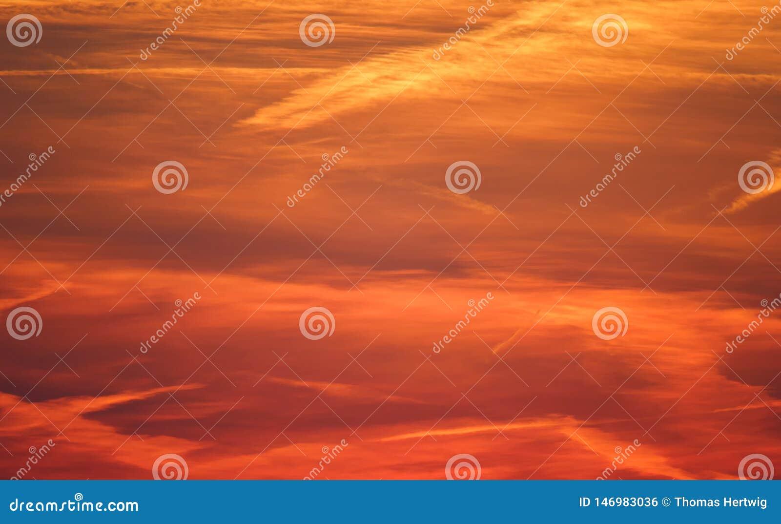 Cielo crepuscolare del cloudscape rosso e drammatico, tramonto leggero dorato